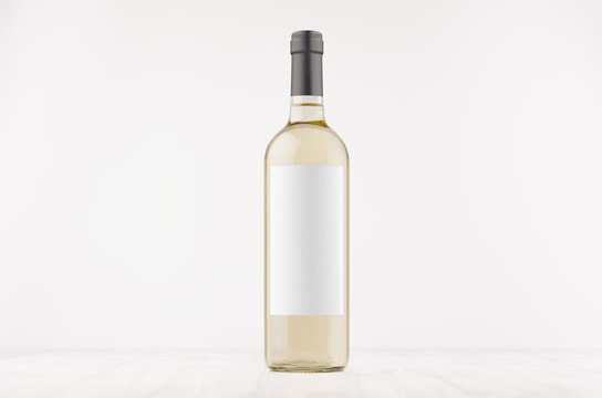 Transparent white wine bottle with blank white label on white wooden board, mock up. Template for advertising, design, branding identity.