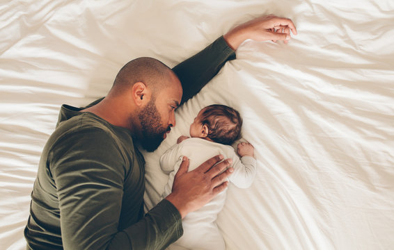 Newborn baby boy sleeping with his father on bed