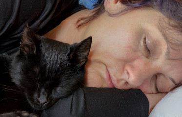 Women and cat sleep together in bed