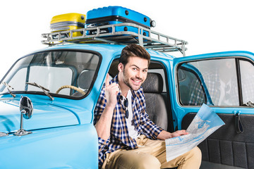 man sitting in car with map