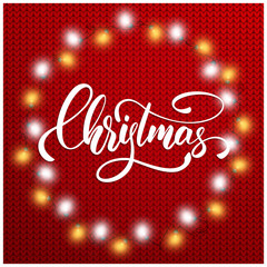 Christmas. Christmas lettering text on knitted sweater background. Realistic Christmas lights and holiday calligraphy