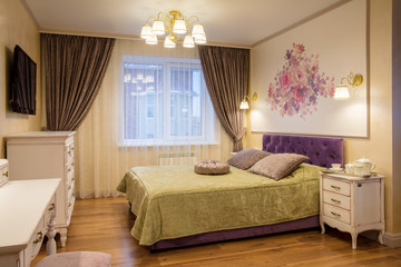 luxurious bedroom in purple and gold colors with window
