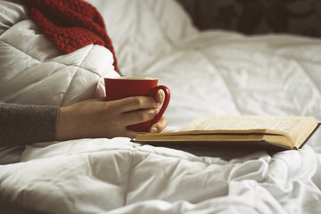 Girl in bed with a book and a cup of tea