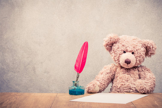 Retro Teddy Bear toy sitting at the old wooden desk with red quill pen in the inkwell and paper sheet front concrete wall background. Vintage style filtered photo