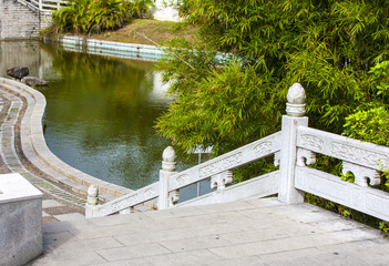 stone staircase with railing and walkway along the pond.