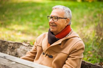 Happy senior man sitting in park and enjoying nature.