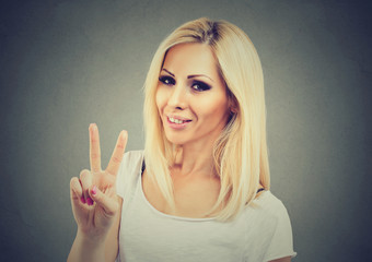 Smiling woman showing victory or peace sign isolated on gray background