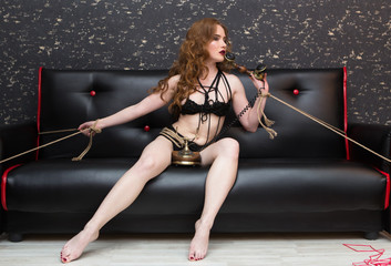 Young attractive woman roped to leather sofa trying to handle telephone hands