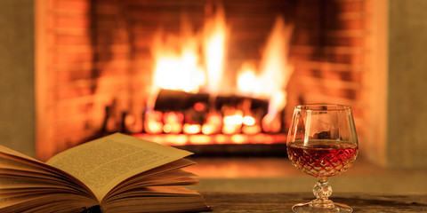 Glass of brandy and a book on burning fireplace background