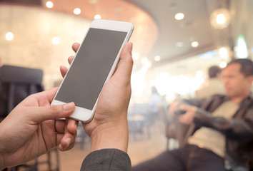 Mockup image of hand holding smartphone with blank white screen in cafe