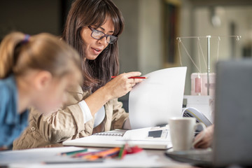Mature woman doing paperwork while daughter drawing at table