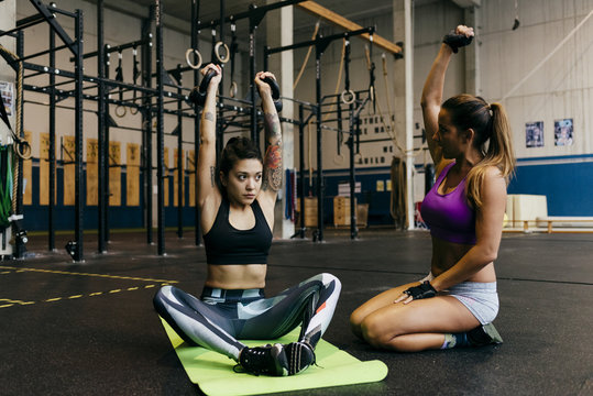 Woman training client in gym
