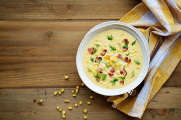 Corn chowder soup with bacon. Brown wooden background. Top view