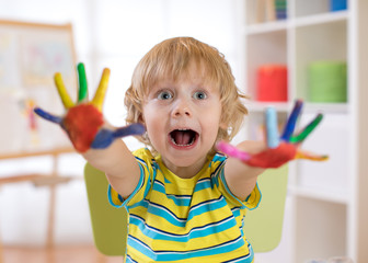 Child boy draws with hands and shows multi-colored painted palms. Children's educational games with paints.