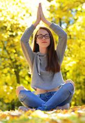 Girl doing yoga in autumn park.