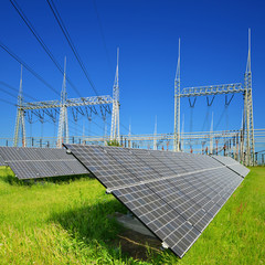 Solar energy panels in the background high voltage power substation. Sustainable resources concept.