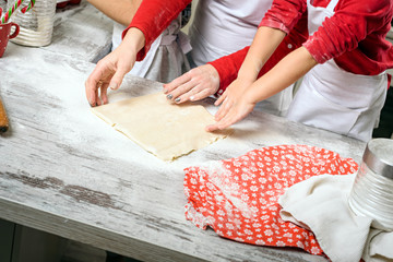 Mother with girls prepare dough for baking