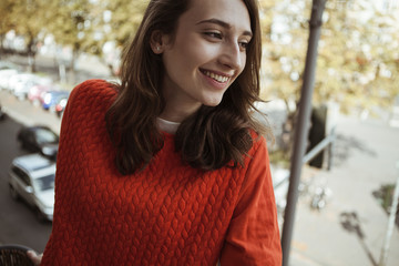Smiling young woman on balcony looking sideways