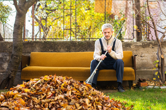 Tired man taking rest from cleaning fallen autumn leaves in the