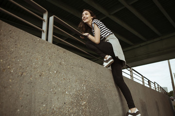 Happy young woman on railing under a bridge