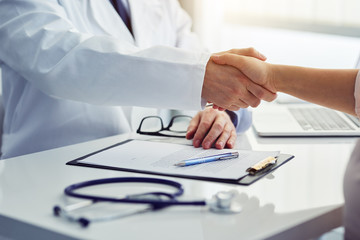 Doctor shakes hands with his patient in the office