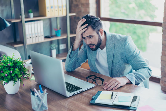 Oh no! Portrait of attractive businessman holding hand on head, looking very disappointed, looking at screen of computer, having mouth opened and disbelieve emotion on his face