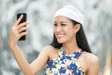 Beautiful toothy smiling young woman in white santa's hat  taking a selfie against blur background
