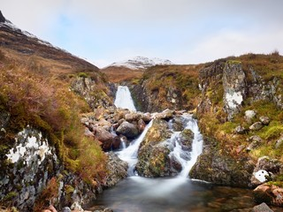 Rapids in small waterfall on stream, Higland in Scotland an early spring day. Snowy mountain peaks