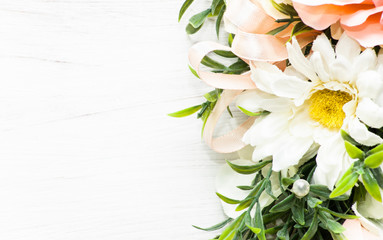 Arrangement of flowers on white wooden background useful as wedding invitation or greeting card
