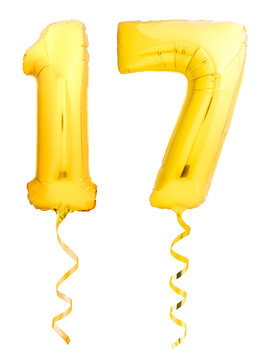 Golden number 17 seventeen made of inflatable balloon with ribbon isolated on white