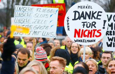 """Employees of insolvent carrier Air Berlin protest with posters reading """"Thanks for nothing Merkel"""" in front of Chancellery in Berlin"""