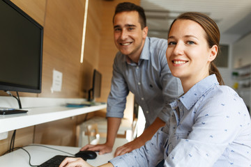 Two office workers sitting in office ad using computer.They working on new project.