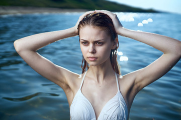 Beautiful young woman bathing in the sea in a swimsuit, vacation, beach, sun, summer