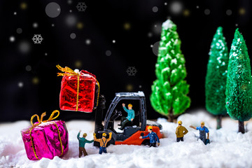 Miniature Worker Passenger Gift Box by Truck on snow floor over dark background with Christ tree ,Decorated Image for Christmas Holiday and Happy New Year Celebration concept.