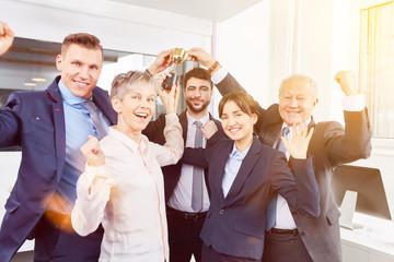 Business Team jubelt über Erfolg mit Pokal
