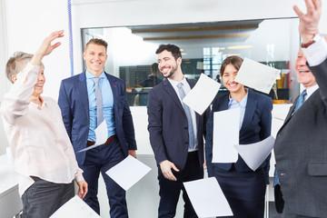Business Team wirft Papiere in die Luft