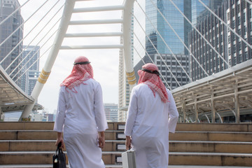Two Arabian meet and talking together in downtown with city background