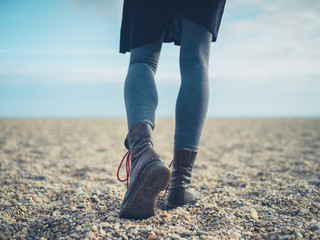 Legs of a woman walking on the beach in autumn