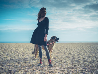 Young woman on beach with giant dog
