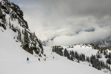 Tourists snowboarding and skiing on snow covered mountain, Whistler, British Columbia, Canada