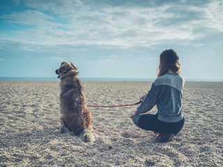 Young woman sitting on beach with big dog