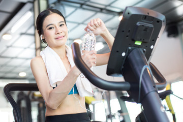 Attractive Asian Woman holding water while exercise bikes at a gym. Woman exercise  Concept.