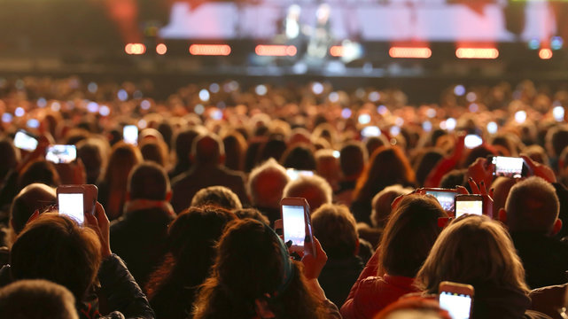many people with smart phones at live concert