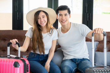 Asian couple travelers prepare luggage for travel trip during long Weekend