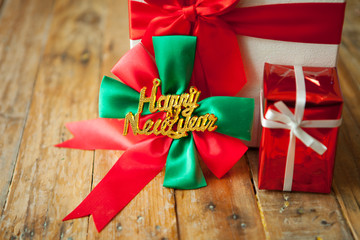 White gift box and red ribbon  on wood background with space..