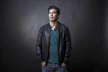 Uomo moro con giacca in pelle e maglietta verde, - sfondo scuro