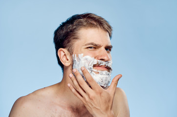 A young guy with a beard on a blue background applies shaving foam