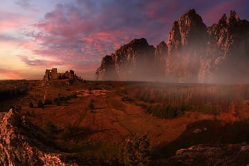 Antyczne ruiny zamku na wzgórzu oświetlone czerwonym zachodem słońca.