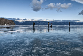 people stand on the ice of lake Baikal and take pictures