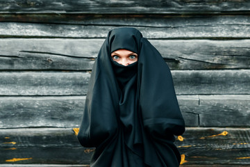 A beautiful, young, Muslim girl in a black veil with a closed face on a gray tree background holds her hands behind her head. Copy space.
